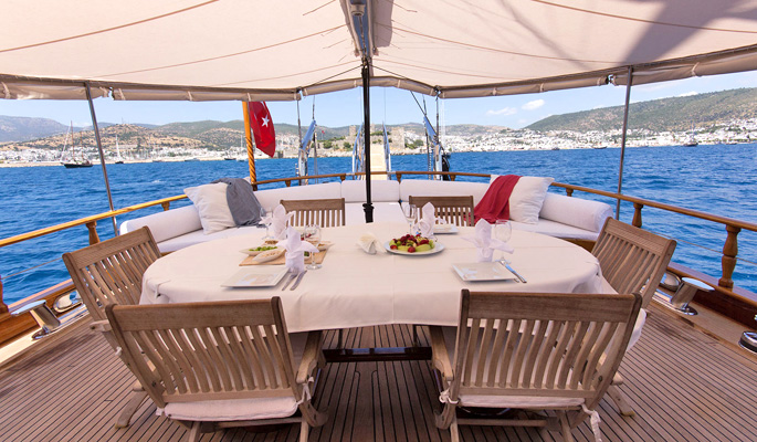 Dining on deck with cushioned sofa for lounging