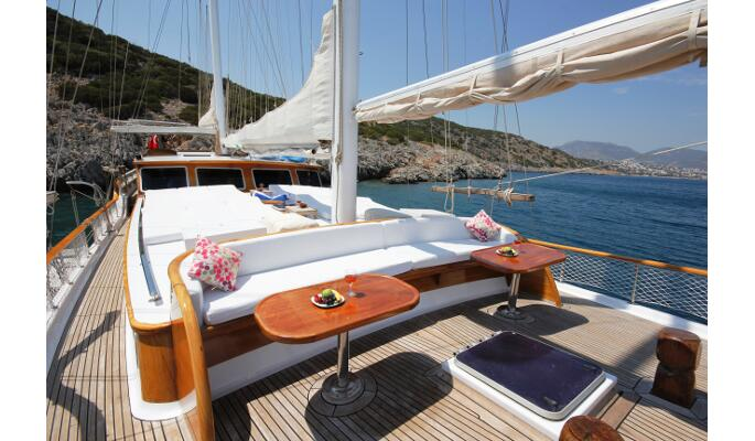 Spacious aft deck with dining area and comfortable sofa for relaxing