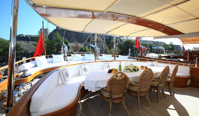 Large shaded on deck dining area and relaxing cushioned area at the aft